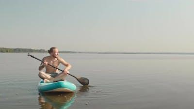 Man on Sup Board Paddling in Lake