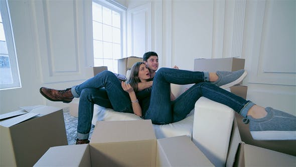 Thumbnail for Couple In Love Hugging Lying Down Among The Boxes
