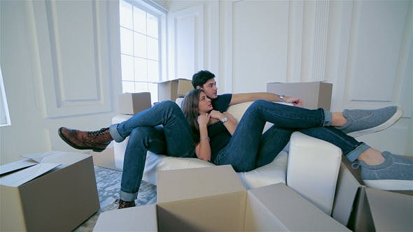 Thumbnail for Couple In Love Lying On Sofa Among Boxes