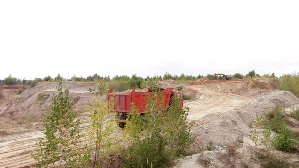 Unloaded truck is driving along iron ore quarry. Mining industry