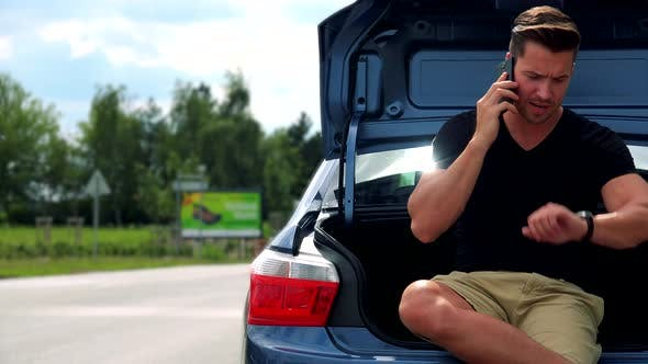Thumbnail for Young Handsome Man Sits in Car Trunk and Phones with Smartphone - Road with Cars