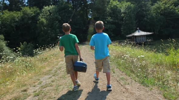 Two boys walking to fishing spot