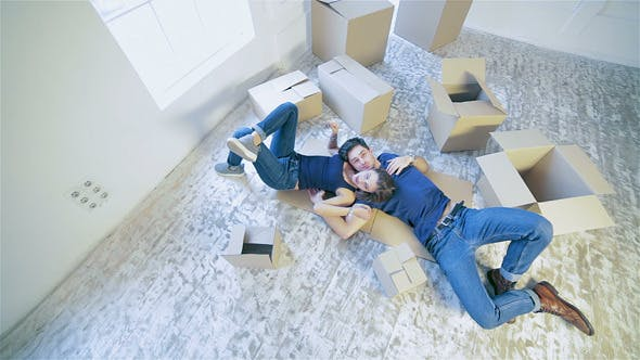 Thumbnail for Couple Lying On The Floor Among The Boxes