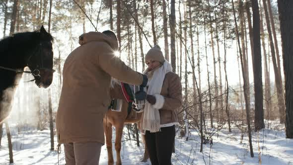 Thumbnail for Couple Drinking Hot Tea during Horseback Riding in Winter Forest