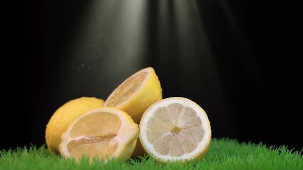 Thumbnail for Sun Rays Shine on Halves of Yellow Lemons Against Black Background