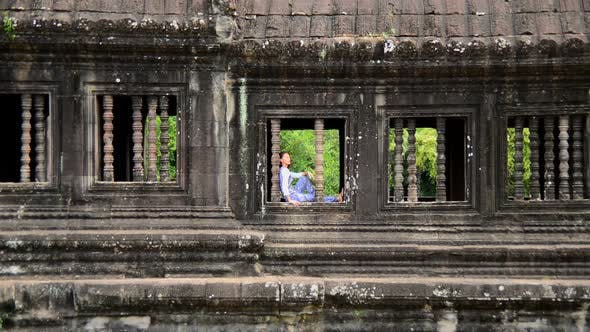 Thumbnail for Female Buddhist Meditating In Window - Angkor Wat, Cambodia