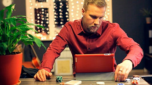 Thumbnail for Man Playing Online Poker in a Beautiful House