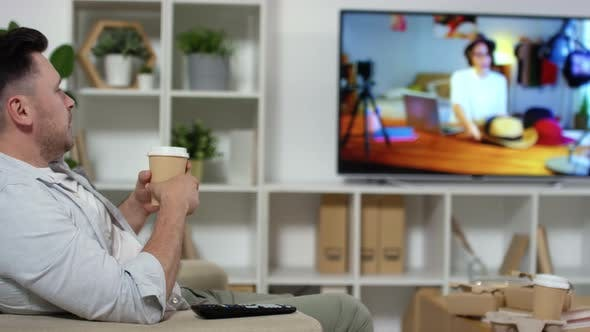Thumbnail for Man Drinking Coffee from Paper Cup in Front of TV at Home