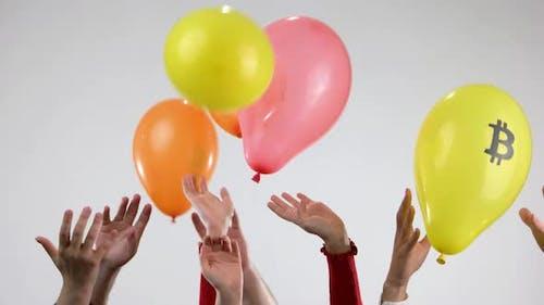 Menschliche Hände werfen Ballons mit Symbolen der Kryptowährung