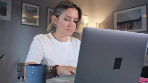 Woman working on laptop computer in home office.