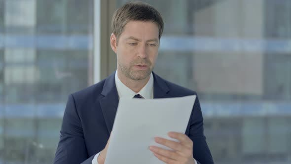 Thumbnail for Businessman Studying Documents at Work