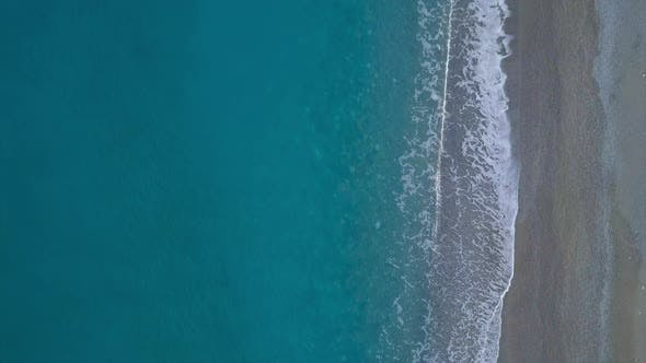 Cover Image for Top Down View Turquoise Waves Reaching Shore Break on Empty Pebble Beach. Pure Sea Aerial