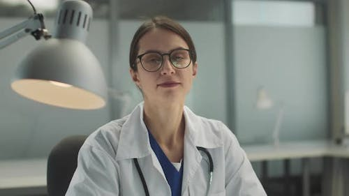 In a Private Clinic Before an Appointment a Female Doctor Puts on Glasses and Looks at the Camera