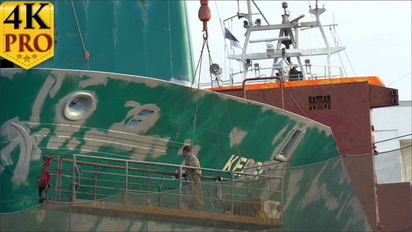 A Ship Worker Repainting Some Green Parts