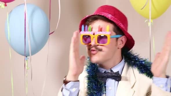 Thumbnail for Nahaufnahme eines lustigen Mannes, der mit Geburtstagssonnenbrille und rosa Hut tanzt