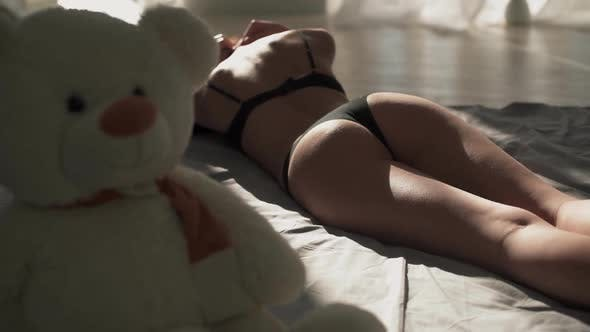 Cover Image for Young Woman with Perfect Body in Lingerie Lying on the Bed. Teddy Bear on the Background of a Naked
