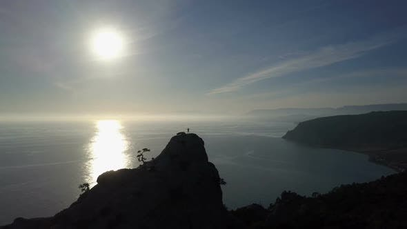 Thumbnail for Aerial Silhouette of Young Woman on the Top of a Mountain Facing the Sea. Flight Over Lady on the