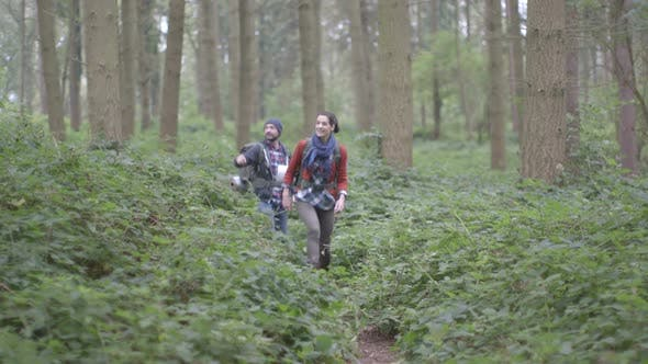 Thumbnail for Couple carrying rucksacks and walking through dirt Tracking Left in forest