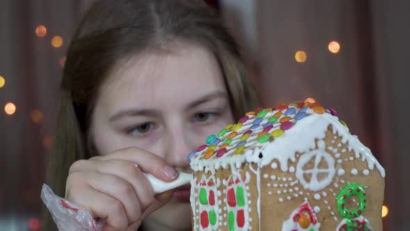 Thumbnail for Girl Decorates a Christmas Gingerbread House