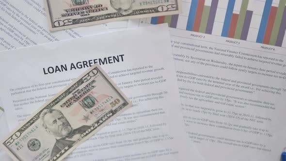 Thumbnail for Top View of Dollars Falling on Loan Agreement, Rain