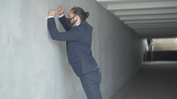 Thumbnail for Side View of Angry Young Businessman in Covid-19 Face Mask Hitting Urban Underground Crossing Wall