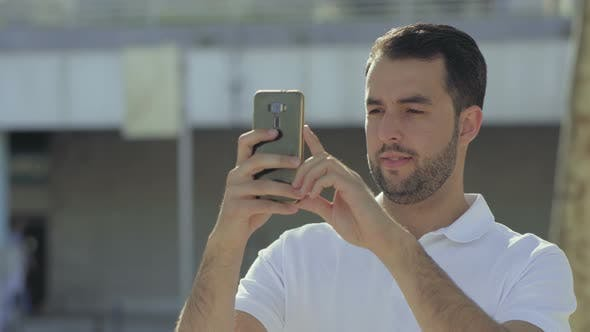 Thumbnail for Smiling Bearded Man Holding Smartphone and Looking at Camera