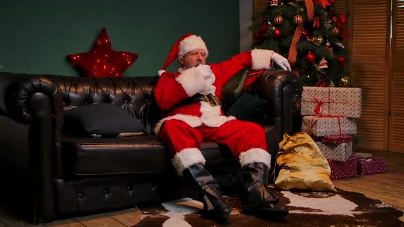 Tired Santa Claus Yawns and Falls Asleep Sitting on the Couch
