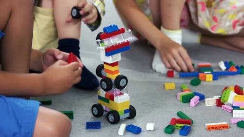 Close Up Kids Playing with Block Toys in Nursery School
