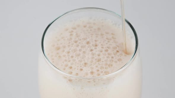 Thumbnail for Pouring lager beer with bubbles and froth over the top in glass over white background