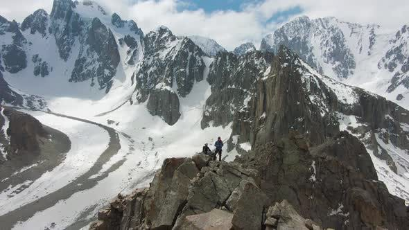 Thumbnail for Two Climbers on Peak of Rock. Snow-Capped Mountains. Aerial View