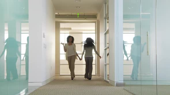Thumbnail for Two businesswomen dancing in office hallway giving a high five