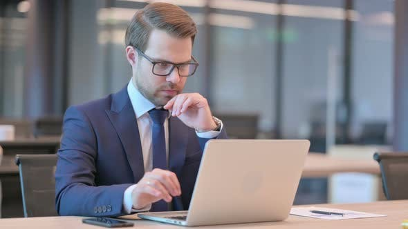 Businessman with Laptop Thinking at Work
