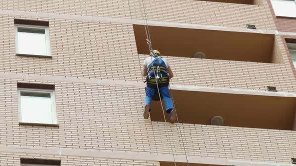 Climber Spends Repair Work on a Multi-storey Building Height