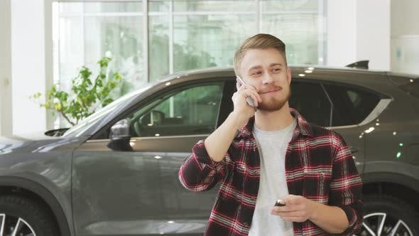 Thumbnail for Happy Young Man Talking on the Phone After Buying a New Car at the Dealrrship