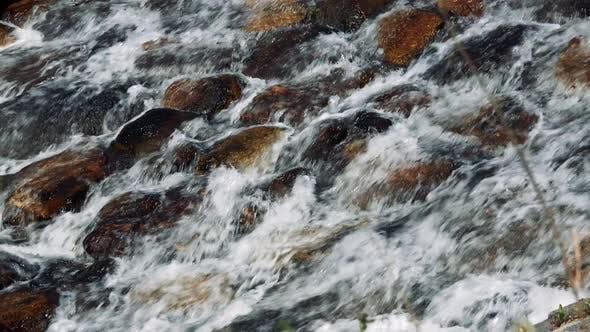 Stream Flows in Stone Riverbed - Closeup