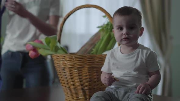 Thumbnail for Ein kleiner Junge sitzt in der Nähe der Korb auf dem Tisch und isst