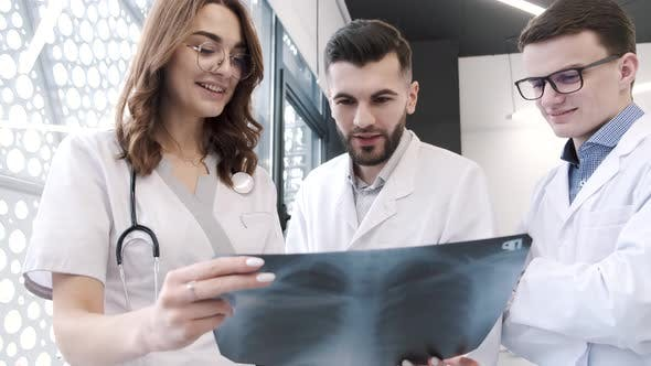 Ärzte in Schutzkleidung Blick auf Röntgenbilder der Lunge