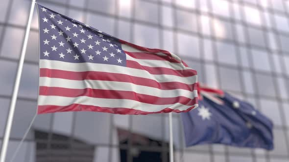 Waving Flags of the USA and Australia in Front of a Skyscraper