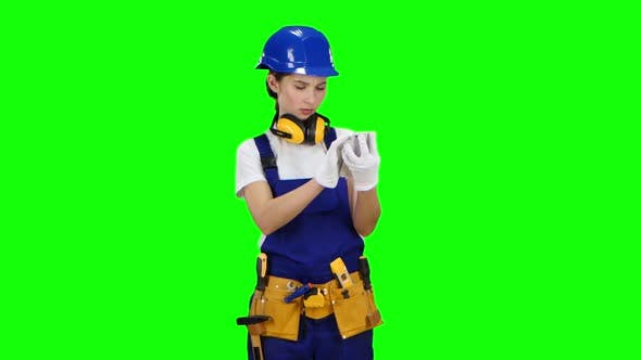 Thumbnail for Girl Builder Looks at Her Smartphone Photo Buildings for Future Work, Green Screen