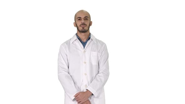 Thumbnail for Standing young serious arab doctor on white background.