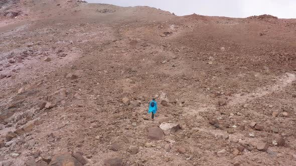 Woman or backpacker hiking up a slope with many loose rocks to reach the tope of the mountain
