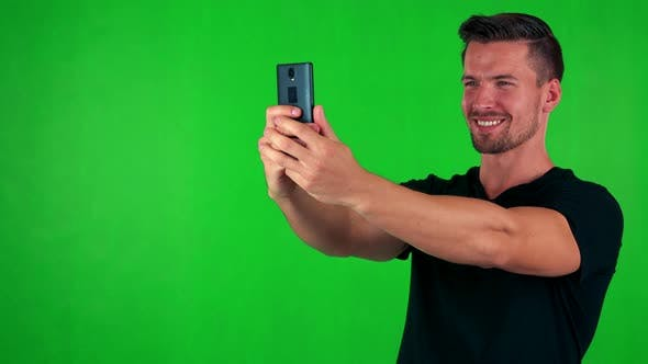 Thumbnail for Young Handsome Caucasian Man Photographs with Smartphone (Selfie) - Green Screen