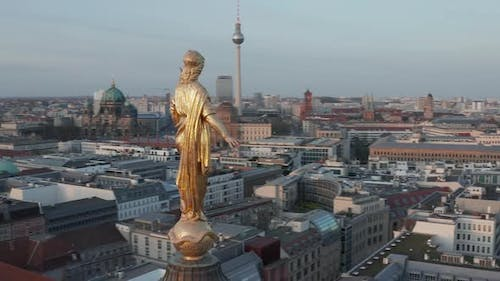 AERIAL: Golden Statue Close Up on Church Cathedral Rooftop in Berlin, Germany with Alexanderplatz TV