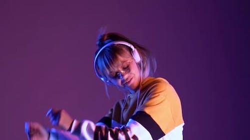 Happy Teen Girl Model Wearing Headphones Listening Music Dancing in Purple Neon