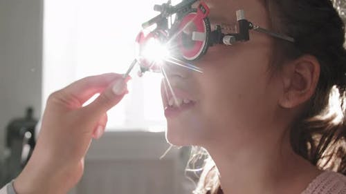 Optometrist Checking Girl Vision With Trial Frame