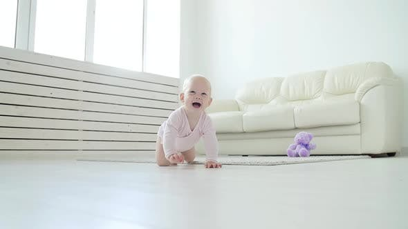 Adorable Baby Girl Learning To Crawl in White Sunny Room.