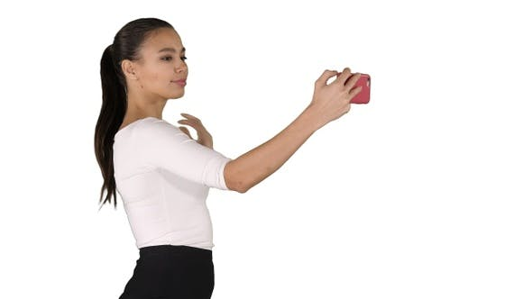 Cover Image for Pretty girl taking a selfie and walking on white background.