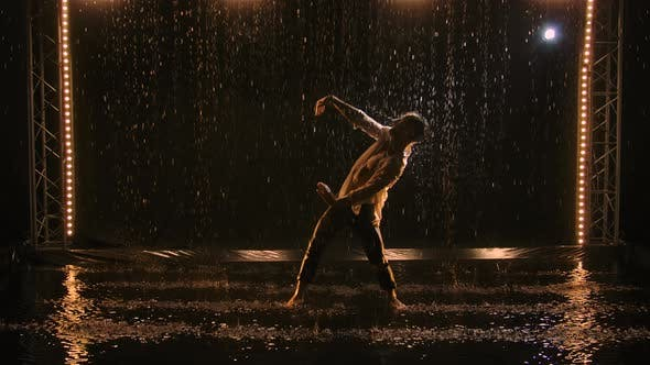 Sexy des jungen Mannes tanzt im Regen im aufgeknöpften weißen Hemd