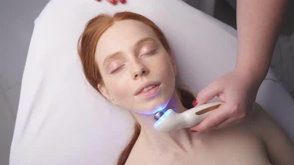 Eine attraktive Frau in einem Kosmetologie-Verfahren in einem Schönheitssalon. Hardware-Kosmetologie