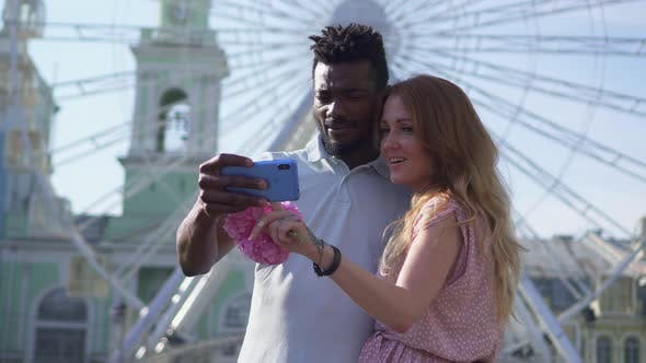 A Cheerful Couple Looks at the Smartphone Screen and Laughs in the Square